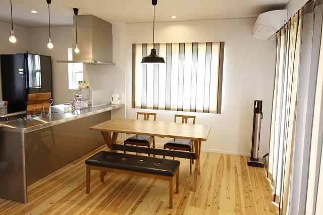 無垢の床、アンティークなテーブルや照明、無機質なステンレスキッチンの融合