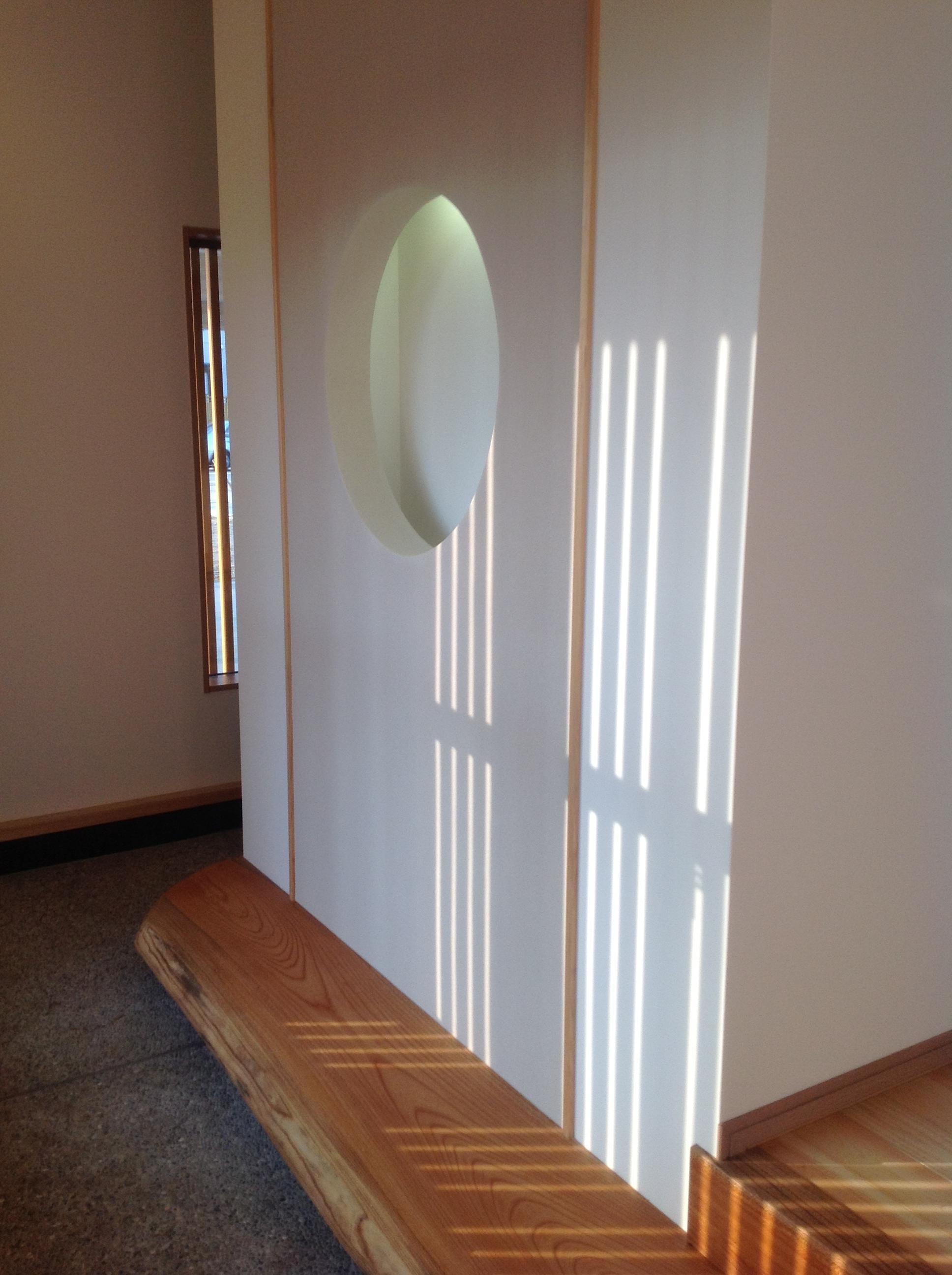 【玄関ホール】お客様を出迎えるのは、多くの無垢材と格子が作り出す陰影 。夜には玄関にお月様が浮かびあがる細工が